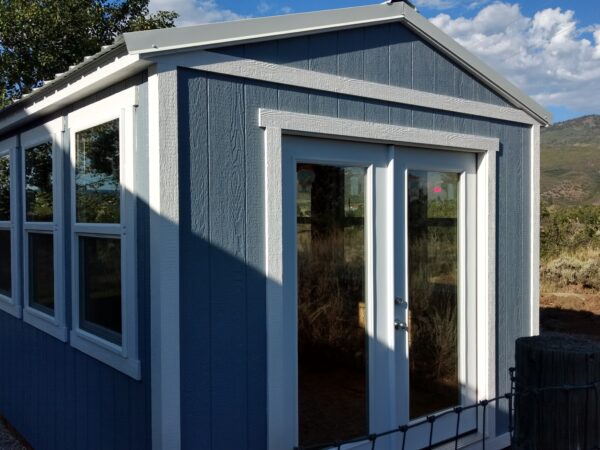 Ranch Style wood shed with french doors, windows, and painted
